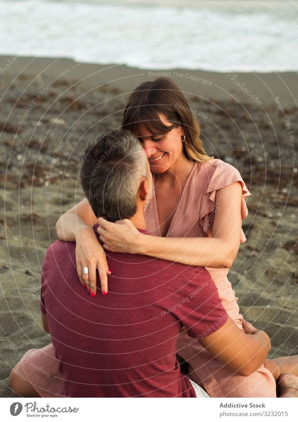 Delighted couple sitting on beach resort love hug date sea smile happy vacation man woman adult honeymoon summer shore coast relationship water embrace ocean