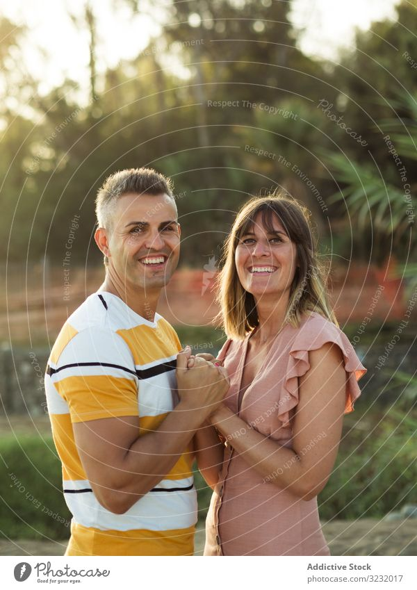 Happy couple looking at each other on beach resort love smile happy holding hands vacation sunny daytime man woman adult honeymoon summer nature shore coast