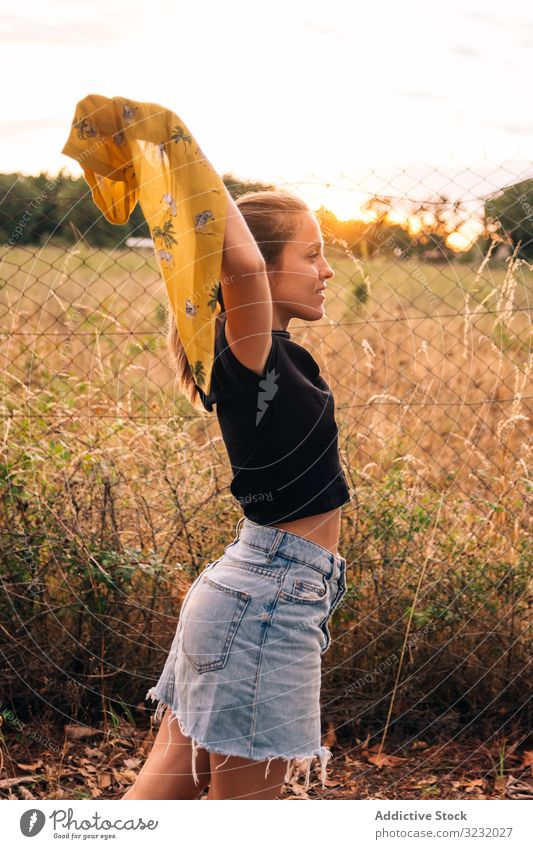 Happy female on meadow in summer woman field happy content casual shirt romantic take off bronzed fence metal chain link nature countryside beauty leisure