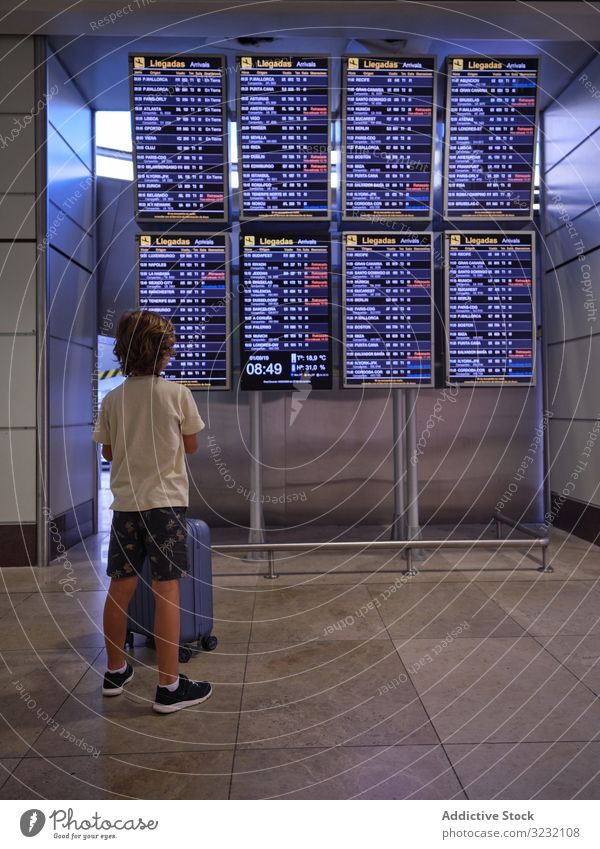Child reading schedule in hall of airport boy suitcase scoreboard look child portugal travel tourist luggage departure arrival trip journey passenger wait