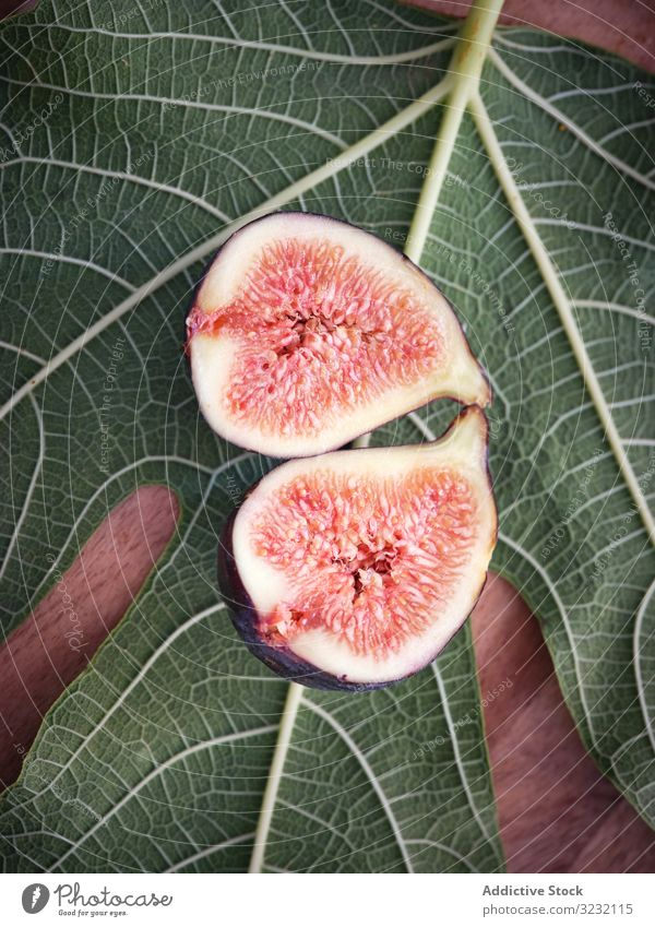 pieces of fig over table and green leaves leaf mature rustic fresh fruits rural tree food wooden traditional closeup spain home edible figs ripe bright