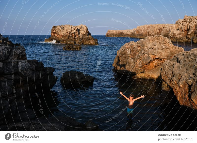 Active kid in diving mask standing in sea water boy ocean cliff rock dive picturesque arms raised shore surface seashore summer boulder journey travel lifestyle