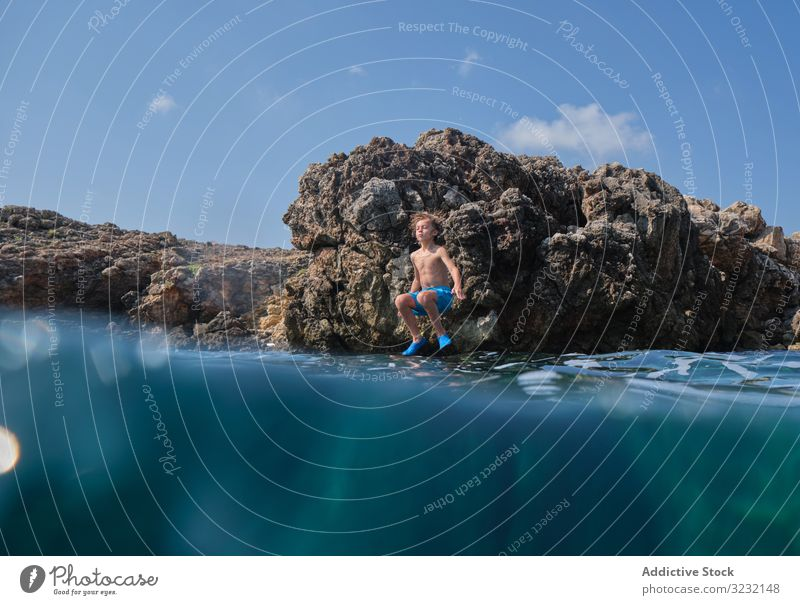 Little kid jumping into sea cliff boy ocean shore active water enjoy summer sky sportive wave motion sunny excited coast rock travel stone vacation child ripple