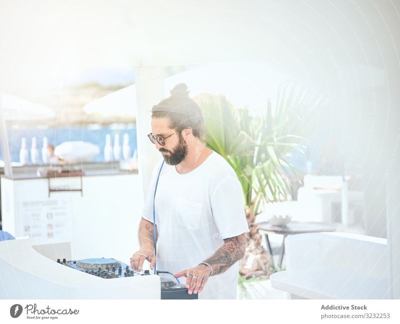 DJ playing music at party man dj headphones fun controller set turntable mix song gig concert electronic event summer leisure job hobby male handsome hipster