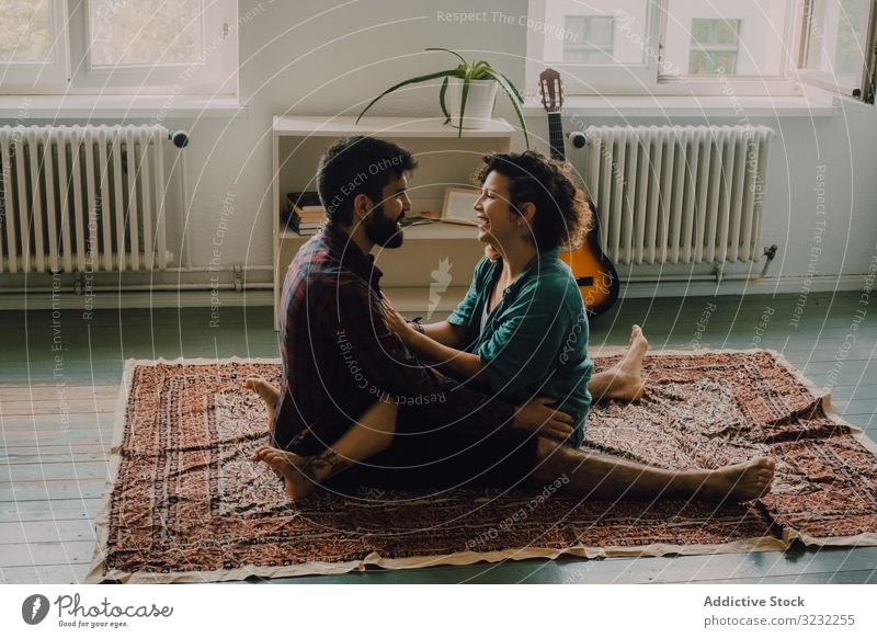 Loving couple embracing while sitting on apartment floor embrace loving cuddling tender casual smile carpet home love together happy hug romantic relationship