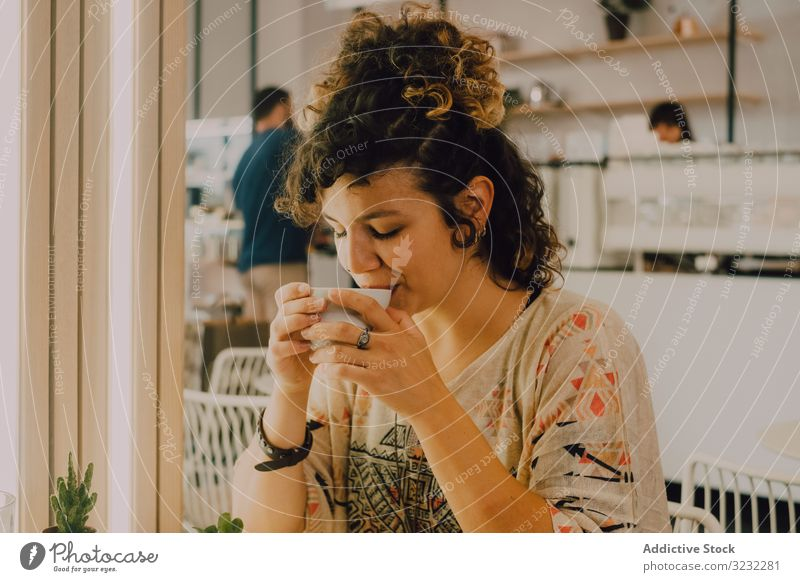 Positive woman drinking coffee in cafe positive happy smile sip mug modern joyful pleased cheerful coffee shop playful young adult hot drink beverage tea