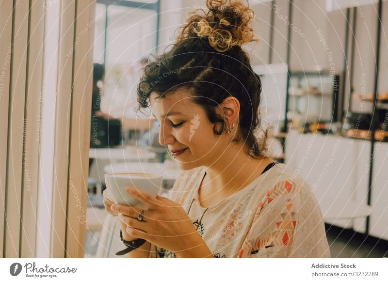 Positive woman drinking coffee in cafe smelling positive happy smile sip mug modern joyful pleased cheerful coffee shop playful young adult hot drink beverage