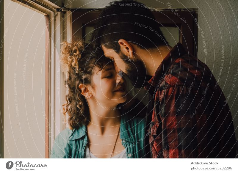 Happy couple embracing on window sill at home embrace happy windowsill joyful smile casual hug hipster modern tender affection lover relationship together