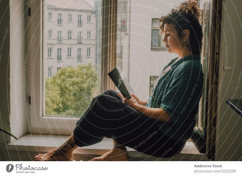 Interested woman reading book at window sill at home interested relaxed literature windowsill barefoot casual sit apartment happy resting young adult peaceful