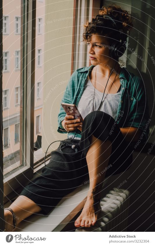 Relaxed woman in headphones using smartphone at home smile pensive listen happy music browsing window sill curly attractive peaceful relaxed apartment young