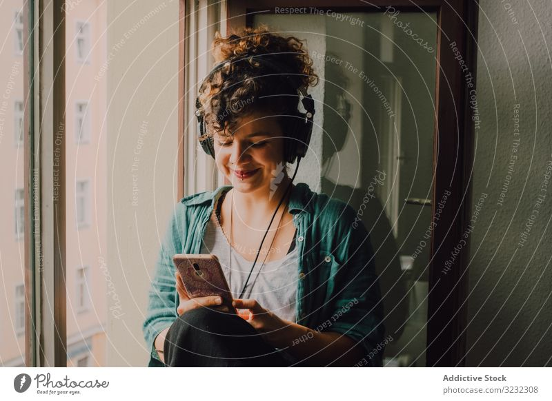 Cheerful woman in headphones using smartphone at home cheerful smile listen happy music browsing window sill curly attractive peaceful relaxed apartment young