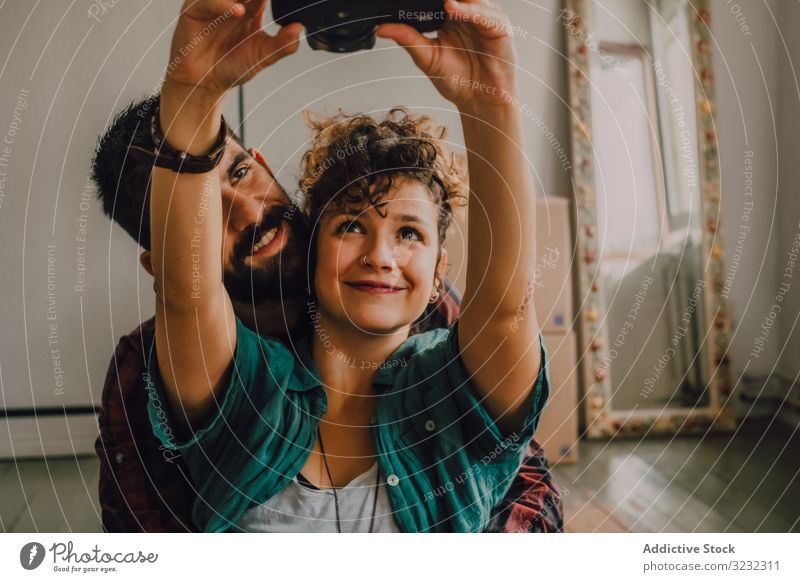 Joyful couple embracing and taking selfie on camera at home hipster joyful affection hugging using photo sit rest floor apartment cuddling house domestic smile