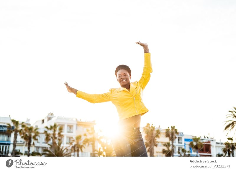 Joyful female smiling and jumping woman happy bounce hands up stylish joyful african american smile jacket bright cute attractive positive healthy charming fit