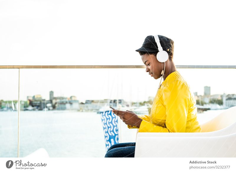 Black woman using mobile phone stylish african american female jacket bright cute attractive positive healthy young pretty modern cheerful relax chill beauty