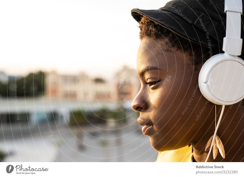 Peaceful female enjoying music and relaxing on balcony woman headphones peaceful content trendy african american lean glass jacket listen happy sound young