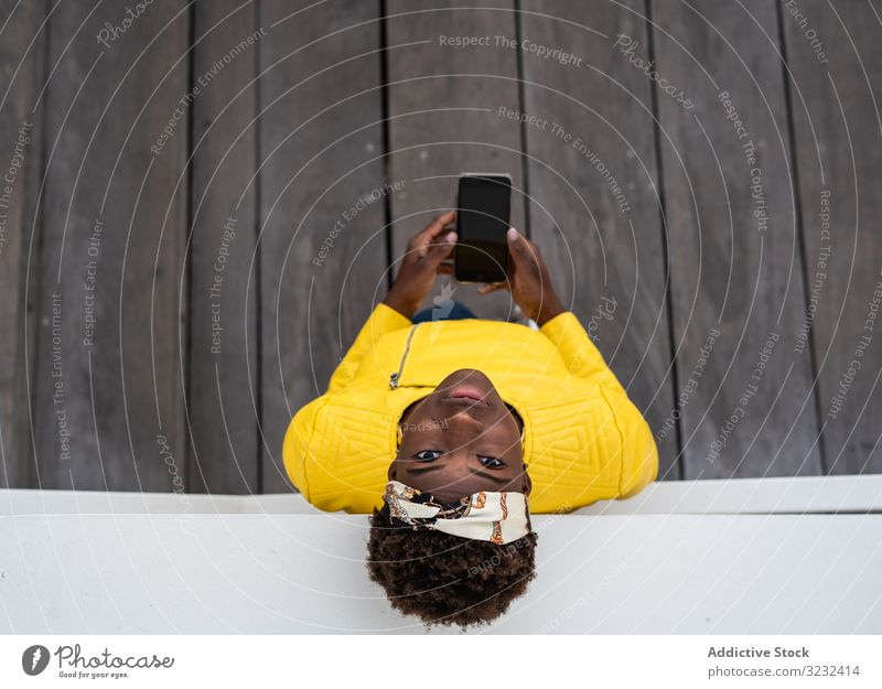 Tranquil female using mobile phone woman modern relax lean city street tranquil african american wall building young leisure happy think contemplation casual