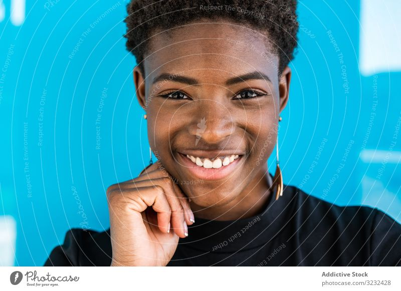 Black woman standing on blue background cool content female african american happy summer cheerful smile beauty style holiday young street attractive joy