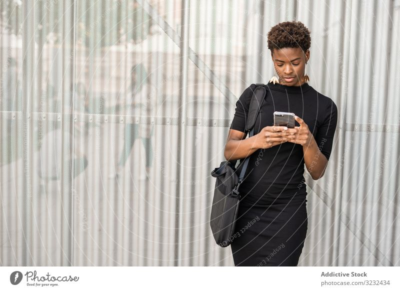 Concentrated female using mobile near urban building woman smartphone message street african american focused concentrated stylish dress black social media