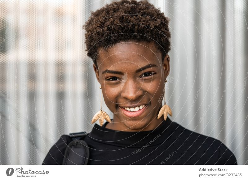 Concentrated female using mobile near urban building woman street african american stylish black happy smile modern casual beautiful cheerful city relax