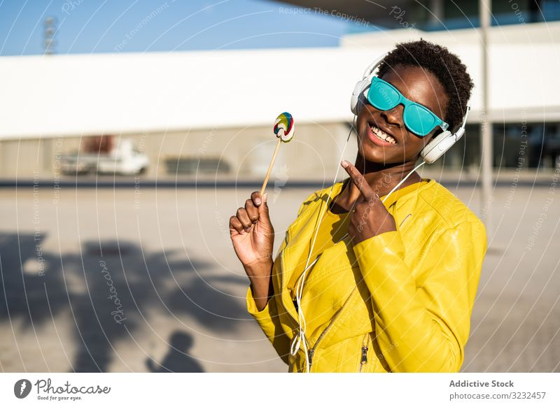 Black woman eating candy lollipop cool trendy african american female jacket yellow sunglasses enjoy sweet summer fun stick young fashion cute relax chill