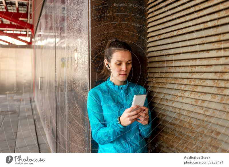 Portrait of beautiful sportswoman holding cell phone healthy active athlete blonde concrete copy space day leaning daylight earphone exercise fit fitness