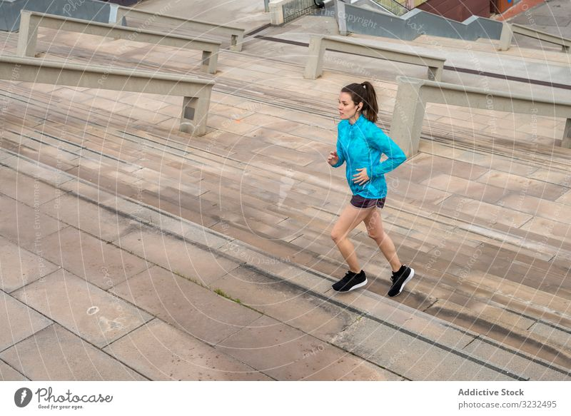 Young runner woman training climbing stairs on the streets of Barcelona healthy sport active female marathon athlete race lifestyle girl fit outdoor fitness