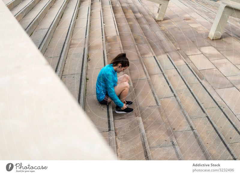 Woman athlete tying her shoelaces on stairs while listening music one person woman part of runner jogger millennial sportswear workout exercise exercising