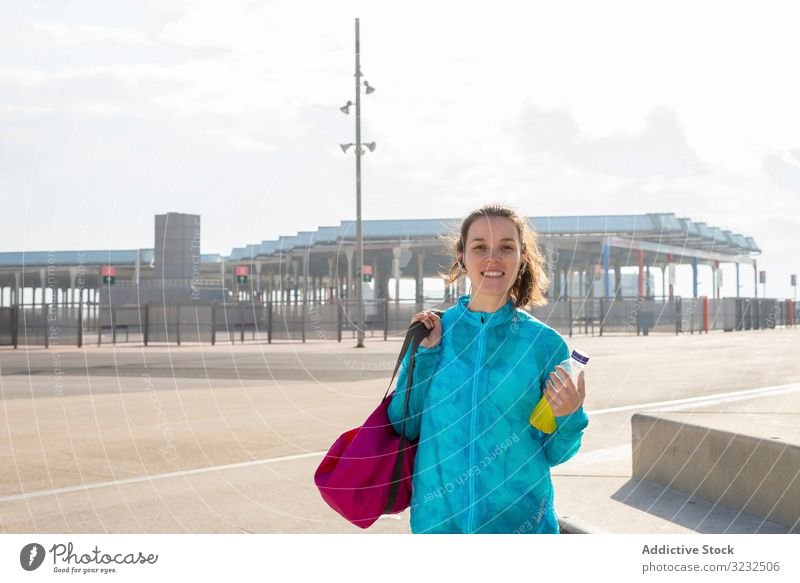 Smiling sportswoman holding bag and bottle while standing outdoor street walking city leisure style outdoors urban activity athlete athletic body carry