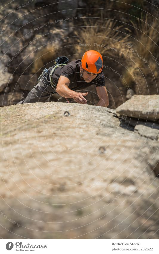 Man climbing a rock man sport mountaineering adrenaline aspiration male difficult strength strong athletic person active sky adventure nature training outdoor