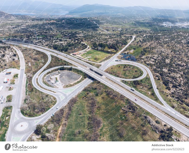 Urban road junction in suburb area countryside urban aerial drone view modern traffic car remote rural valley summer intersection landscape nature lane