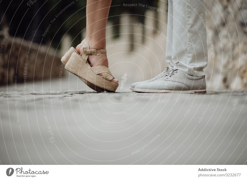 Romantic couple standing facing each other at summer street romantic kiss pebbled valentine pavement tiptoe sandals together relationship casual happy love city
