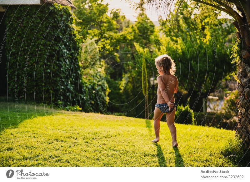 Shirtless girl under spraying water in garden play lawn summer sunny daytime fun child kid little panties shirtless childhood happy joy yard wet drop stream