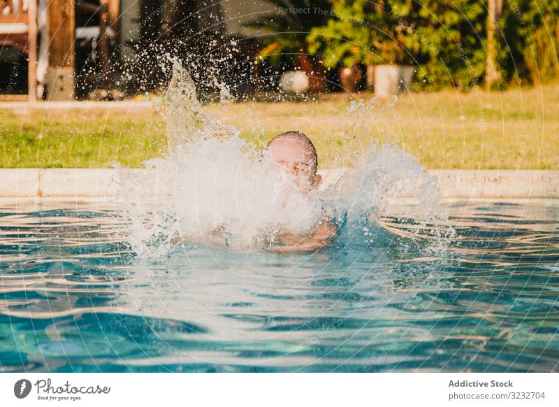 Cheerful girl jumping into pool water scream raised arms fun yard play kid child little hands up panties shirtless garden vacation weekend summer joy happy