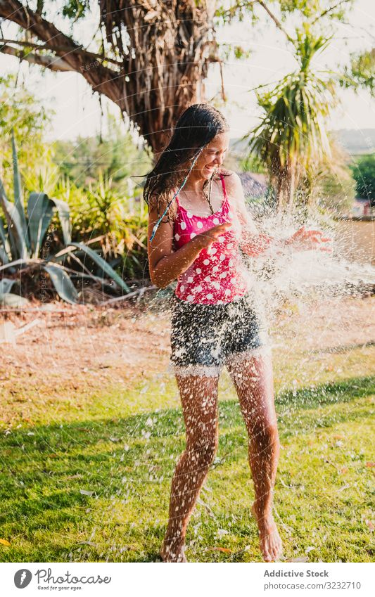 Cheerful teenager having fun with jet of water garden laugh summer weekend girl excited lifestyle rest relax stream clean clear joy delighted optimistic glad
