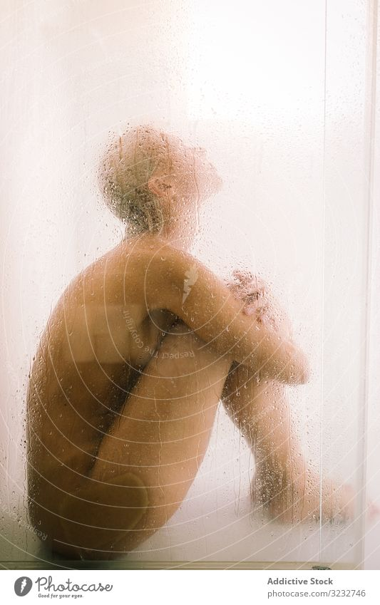 Woman behind wet glass in shower woman transparent partition bathroom water drop young female care body clean clear hygiene sensual translucent skincare routine
