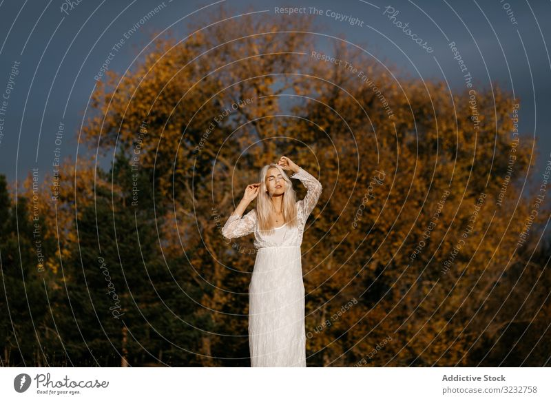 Beautiful blonde woman gazing at autumn countryside inspiration tender beautiful lace content woodland smile contemplation rural orange foliage young adult joy