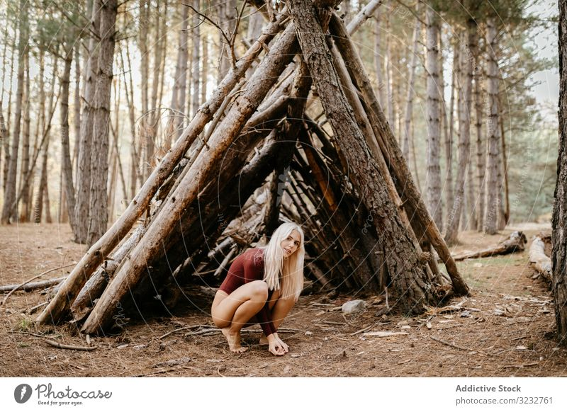 Barefoot woman squatting beside primitive shelter in woods autumn harmony relaxed concept blonde carefree beautiful attractive ecology barefoot trail leotard