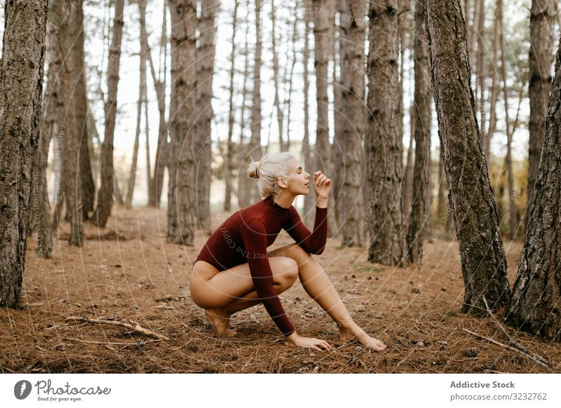 Beautiful modern woman resting barefoot in evergreen forest woods harmony squatting primitive blonde carefree attractive beautiful charming leotard red bright