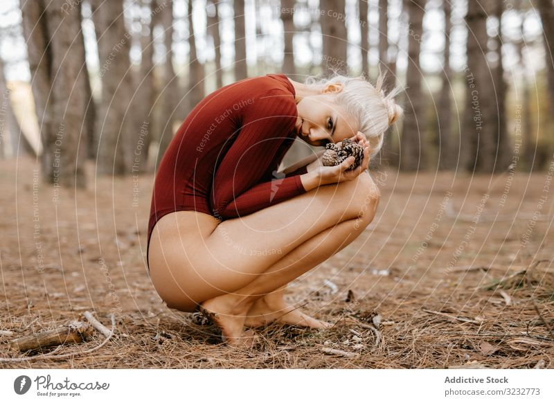 Beautiful modern woman resting barefoot in evergreen forest woods harmony squatting primitive embracing knees blonde carefree attractive beautiful charming