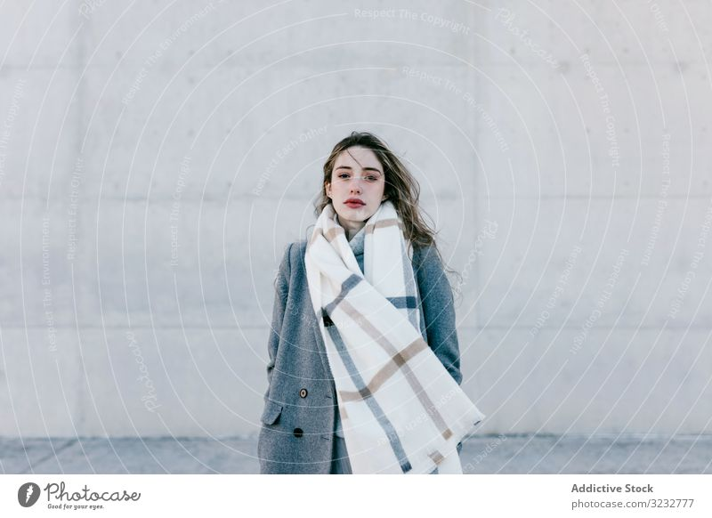 Young woman in coat and scarf on windy day stylish street wall city building female urban fashion cool young model outfit warm weather exterior lady long hair