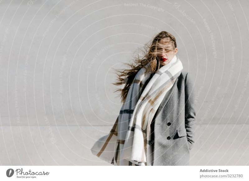 Young woman in coat and scarf on windy day stylish street closed eyes wall city building female urban fashion cool young model outfit warm weather exterior lady