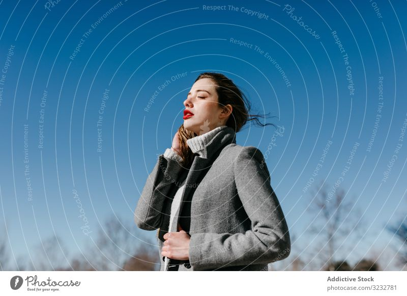 Young woman in coat on windy day stylish street closed eyes female fashion cool young model outfit warm weather exterior lady long hair trendy elegant vogue