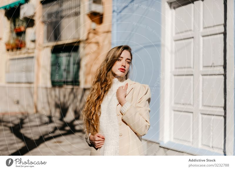 Sensual female standing near windows on the street woman stylish building sunny protection young sensual urban fashion model cool trendy cover blouse elegant