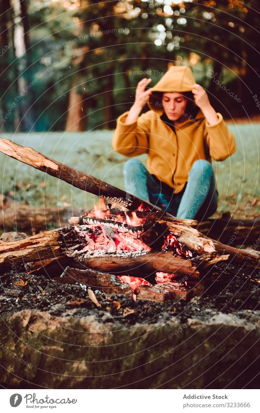 Traveling woman warming hands near campfire on forest glade tranquil flame contemplate relax solitude calm quiet silence firewood freedom enjoy serenity
