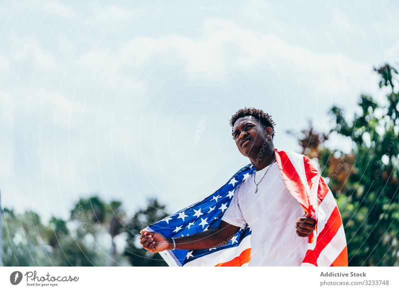Black man wrapping in American Flag outside american flag wrapped black african american national independence active 4th of july banner celebrating freedom