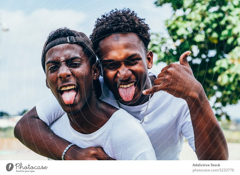 Smiling black friend hugging and grimacing gesturing with hands men showing tongue confident grimace friendship african american funny face crazy happy gesture
