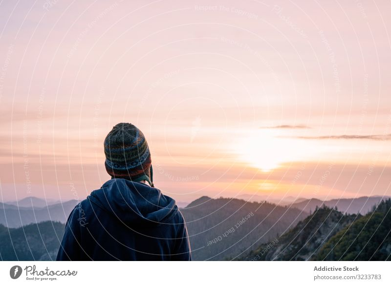 Warmly dressed person looking at sunrise in mountain tourist travel nature landscape sunset adventure tourism rock sky hike top beautiful vacation natural