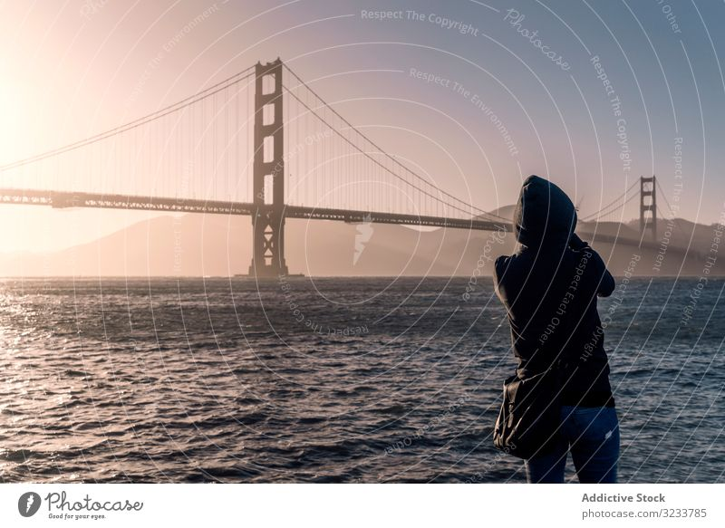 Tourist looking at ocean and large bridge in light day architecture water traditional travel tourist tourism river skyline transportation beautiful summer