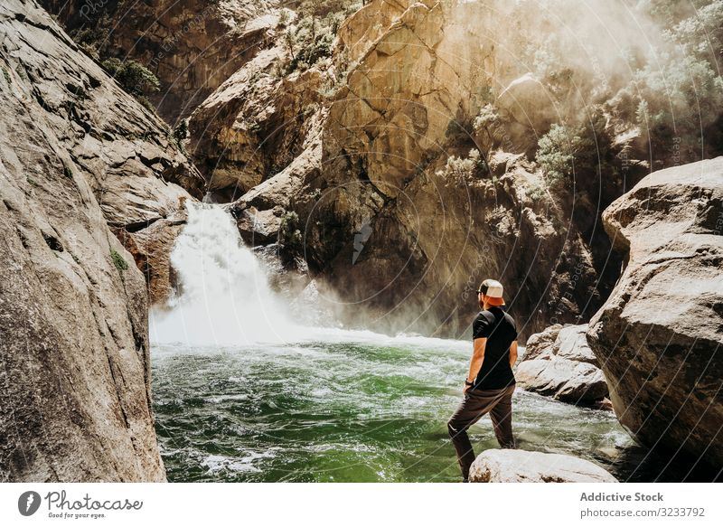 Tourist gazing at mountain waterfall tourist gaze man casual contemplation cascade rocky slope river mist summer sunny stream cliff young adult nature landscape