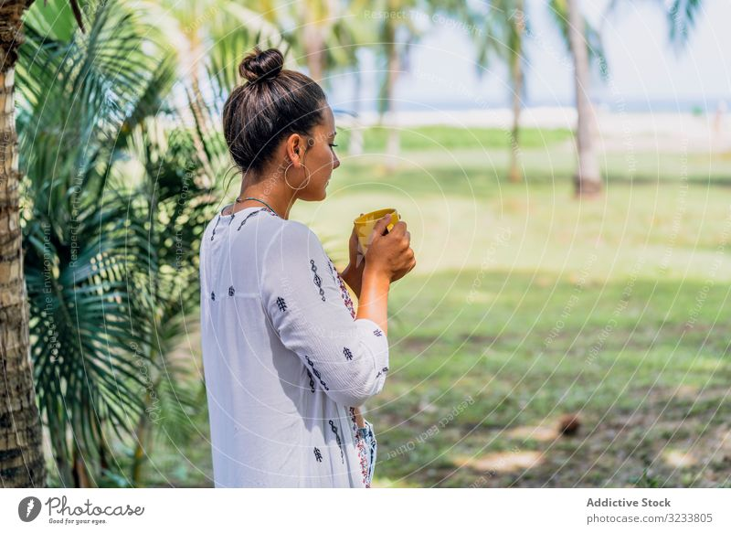 Relaxed woman enjoying hot drink and standing on exotic lawn relaxed seaside palm tree sunny peaceful coffee mug grass tropical rest costa rica young tanned
